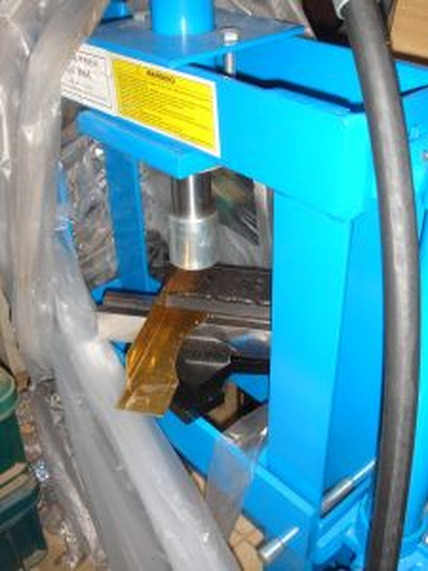 油圧プレスで曲げ加工中の灰受け